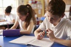 Zwei Kinder, die oben an ihren Schreibtischen in der Grundschule, Abschluss arbeiten Stockbild