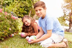 Zwei Kinder, die Osterei Hunt In Garden essen Stockbilder