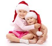 Zwei Kinder, die rote Weihnachtsschutzkappen und -lächeln tragen Stockfoto