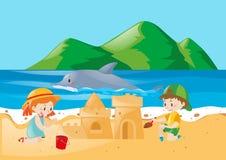 Zwei Kinder, die Sandburg auf dem Strand spielen Lizenzfreies Stockbild