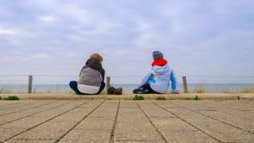 Zwei Kinder, die sich auf den Pflasterungen hinsetzen und das Meer, dick kleidend mit blauem Himmel mit weißen Wolken auf einen  lizenzfreie stockfotografie