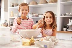 Zwei Kinder, die Spaßbacken in der Küche haben Stockbild
