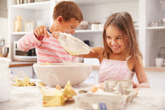 Zwei Kinder, die Spaßbacken in der Küche haben Stockfotos