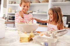Zwei Kinder, die Spaßbacken in der Küche haben Stockfotografie