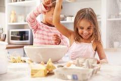 Zwei Kinder, die Spaßbacken in der Küche haben Lizenzfreie Stockfotografie