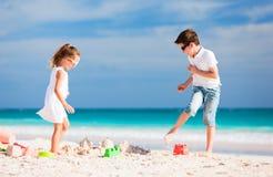 Zwei Kinder, die am Strand spielen Stockbild