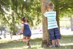 Zwei Kinder, die Verstecken im Park spielen Stockfotos