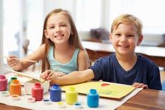 Zwei Kinder, die zu Hause Bild malen Stockfotografie