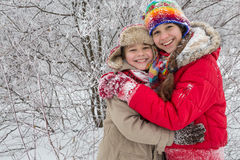 Zwei Kinder, die zusammen auf Winterwald stehen Stockfotografie