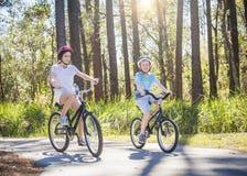 Zwei Kinder, die zusammen Fahrräder draußen an einem sonnigen Tag reiten Lizenzfreie Stockbilder