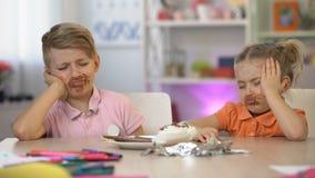 Zwei Kinder geschmiert mit sitzender Tabelle der Schokolade, Magenschmerzen, essend zu viel stock footage
