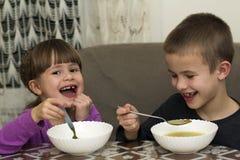 Zwei Kinder Junge und Mädchen, die Suppe mit Löffel von eine Platte wi essen Stockbild