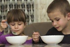 Zwei Kinder Junge und Mädchen, die Suppe mit Löffel von eine Platte wi essen Lizenzfreie Stockfotografie