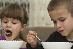 Zwei Kinder Junge und Mädchen, die Suppe mit Löffel von eine Platte wi essen Lizenzfreies Stockbild