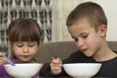 Zwei Kinder Junge und Mädchen, die Suppe mit Löffel von eine Platte wi essen Lizenzfreie Stockbilder