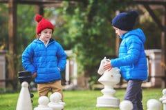Zwei Kinder, Jungenbrüder, Schach mit enormen Zahlen in t spielend Stockfotos