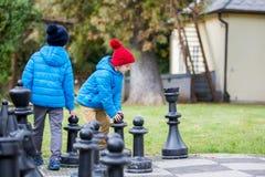 Zwei Kinder, Jungenbrüder, Schach mit enormen Zahlen in t spielend Stockfotografie