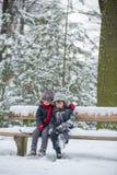 Zwei Kinder, Jungenbrüder, sitzend auf einer Bank im Park, winterti Lizenzfreies Stockbild