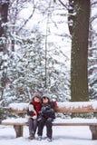 Zwei Kinder, Jungenbrüder, sitzend auf einer Bank im Park, winterti Lizenzfreie Stockfotos