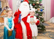 Zwei Kinder kleideten in den Karnevalsklagen mit Santa Claus nahe Weihnachtstannenbaum in neuem Year& x27 an; s-children& x27; s- Stockfotos