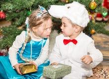 Zwei Kinder kleideten in den Karnevalsklagen nahe Weihnachtstannenbaum in neuem Year& x27 an; s-children& x27; s-Feiertag Lizenzfreies Stockbild