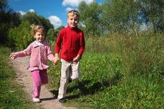 Zwei Kinder laufen gelassen auf Pfad am Sommer Stockbild