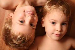Zwei Kinder liegen auf Fußboden Stockfotografie