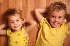 Zwei Kinder liegen auf Fußboden Stockbilder