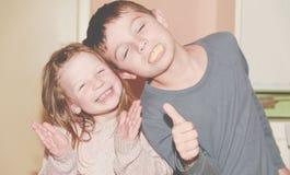 Zwei Kinder machen Gesichter Junge gibt Daumen auf und Mädchen klatscht den Schlag Lustiges und Kinderkonzept Lizenzfreie Stockfotos