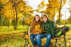 Zwei Kinder mit Blumenstrauß von Ahornblättern Stockfotos
