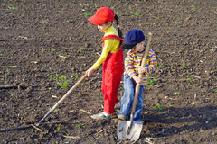 Zwei Kinder mit Gartenhilfsmitteln Stockbilder