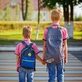 Zwei Kinder mit Rucksäcken gehend auf die Straße, halten Alarmuhr, die oben auf einen Stapel Bücher sitzt Lizenzfreie Stockfotos