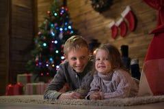 Zwei Kinder nahe einem Weihnachtsbaum lizenzfreie stockfotografie