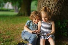 Zwei Kinder sitzen im Park unter einem großen Baum und im Spiel auf der Tablette Stockbild