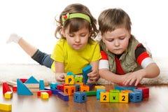 Zwei Kinder spielen auf dem Fußboden Stockfotos