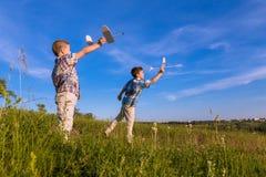 Zwei Kinder starten seine airplans am Feld Stockfotografie