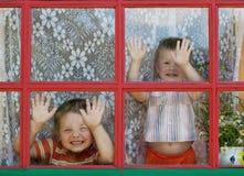 Zwei Kinder täuschen herum und zeigen die Gesichter Stockfotografie