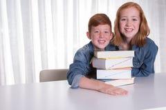 Zwei Kinder und ein Stapel von Büchern Stockbild