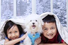 Zwei Kinder und ihr Welpe, die unter Decke liegen Stockfotos