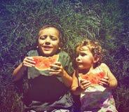 Zwei Kinder, welche die Wassermelone getan mit einem Retro- Weinlese instagram f essen Stockbilder