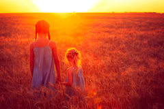 Zwei Kindermädchen am Sonnenuntergangfeld Stockbilder