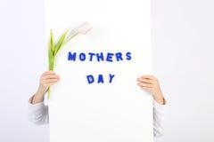 Zwei Kindheitshände, die weißes Brett mit blauem Text Mütter Tag und einer weiße und violette Tulpe halten Stockfotos