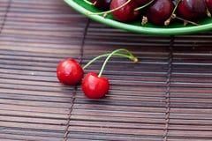 Zwei Kirschen in der Platte auf einer Bambusmatte Lizenzfreies Stockbild