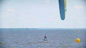 Zwei kitesurfers, die hinter einander auf kiteboards über dem Meer fliegen stock video