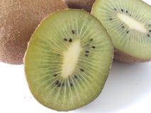 Zwei Kiwistücke auf einem weißen Hintergrund mit ganze Kiwifruits Stockfotografie