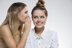 Zwei klatschende Mädchen, man wird intrigiert Stockbild