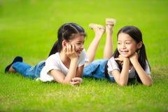 Zwei kleine asiatische Mädchen, die auf das grüne Gras legen Stockfotografie