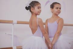 Zwei kleine Ballerinen, die nach Tanzstunde sprechen lizenzfreie stockbilder