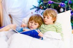 Zwei kleine blonde Geschwisterjungen, die ein Buch auf Weihnachten lesen Lizenzfreie Stockbilder