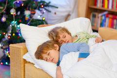 Zwei kleine blonde Geschwisterjungen, die im Bett auf Weihnachten schlafen Stockbilder